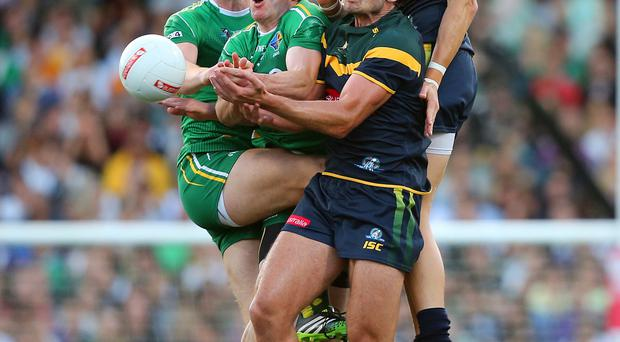 Up close and personal: Ireland's Sean Cavanagh and Aidan Walsh (left) battle with Jobe Watson and Nick Riewoldt in Perth