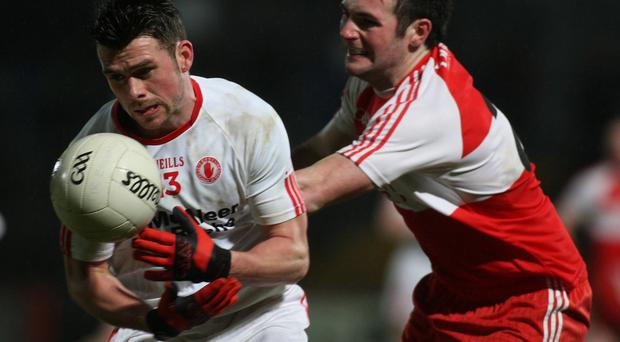 Tyrone's Darren McCurry is tracked down by Derry ace Oisin Duffy