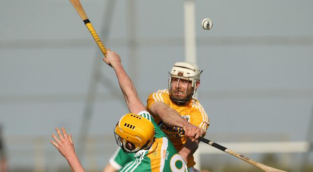 In the air: Antrim's Neil McManus battles for possession with Offaly's Pat Camon