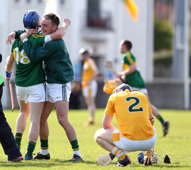Joy and pain: Kerry players celebrate as a dejected Odhran McFadden of Antrim looks on