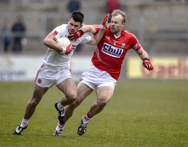 Up close and personal: Darren McCurry of Tyrone attempts to fend off the interest of Cork's Tom Clancy in the Alliance League