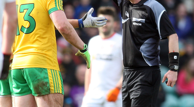 Man in middle: Joe McQuillan, showing a black card to Donegal's Martin McElhinney during the National League encounter with Tyrone, will referee tomorrow's encounter