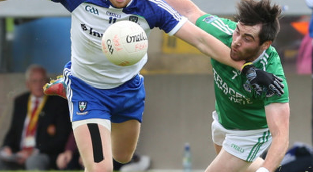 Close quarters: Kieran Hughes of Monaghan is tackled by Fermanagh's Barry Mulrone