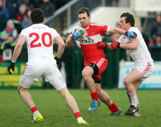 No way out: Ryan Bell of Derry does is best to avoid the tacklers from Tyrone