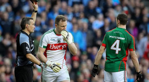 Black day: Maurice Deegan was a busy man at Croke Park on Saturday showing Mayo keeper Robert Hennelly, his team-mate Lee Keegan and Dublin's Jonny Cooper black cards