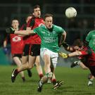 Kicking on: Fermanagh ace Che Cullen moves the ball forward despite the attentions of Down's Aidan Carr