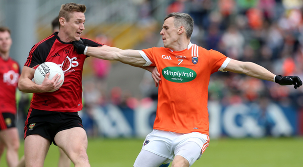 Getting shirty: Down's Caolan Mooney attempts to hold off Mark Shields of Armagh in the Ulster Championship clash