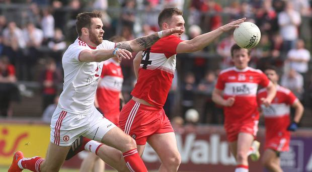 Close tussle: Tyrone's Ronan McNamee (left) challenges Derry's Ryan Bell