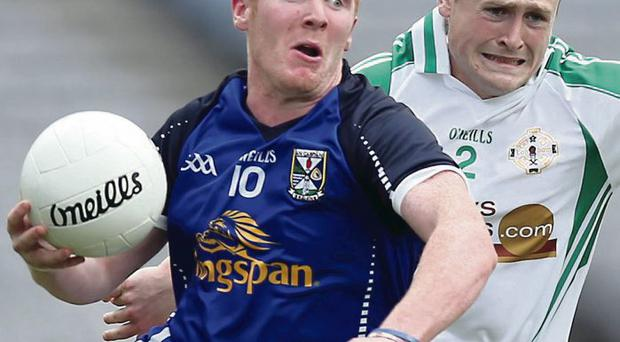 Hold on: Cavan's Cian Mackey clashes with Philip Butler