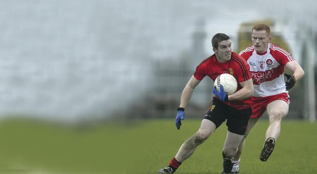 In possession: Derry's Conor McAtamney wrestles with Down's Conleth O'Hare