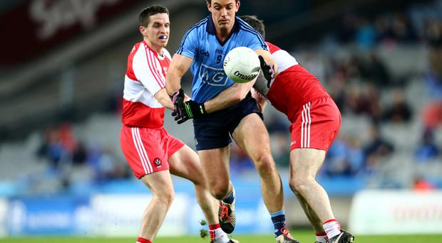 Hanging on: Michael McIver (left) and Oisin Duffy try to stop Dublin's Tomas Brady