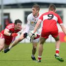 Three's a crowd: Tyrone's Conall Grimes tries to keep possession of the ball while under the close attention of Derry's Brian Cassidy and Oisin McWilliams