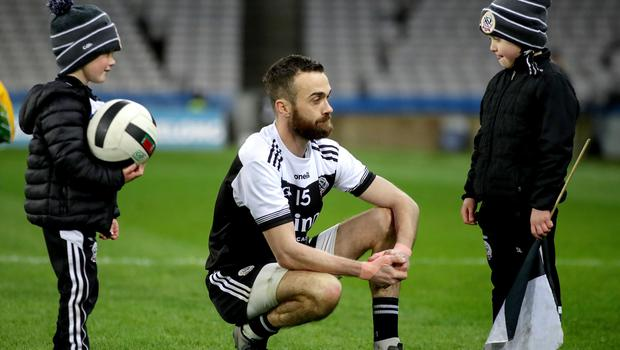 Tough luck: Kilcoo's Conor Laverty is consoled by his sons after the All-Ireland Club football title slipped from his grasp