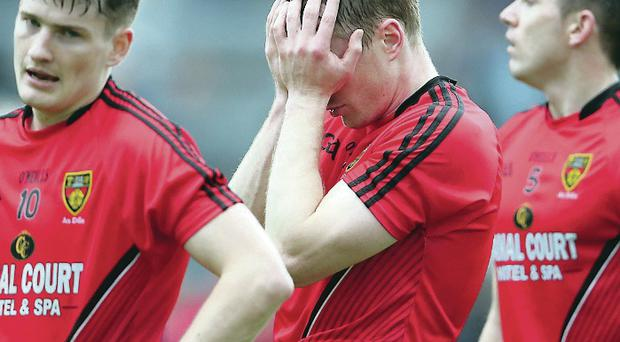 Feeling down: Brendan McArdle and his team-mates show their frustration at having lost against Tyrone