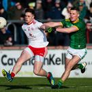 Closed down: Tyrone's Liam Rafferty clashes with Robin Clarke yesterday