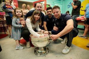 Players Cian O'Sullivan and Rob McDaid meet Paul and Tracy Daly, their children Cara age 3, and Ashling aged nine weeks during a visit to Crumlin Children's Hospital in Dublin yesterday