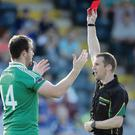 Referee Michael Duffy shows a red card to Fermanagh's Sean Quigley for an incident at the end of the first half