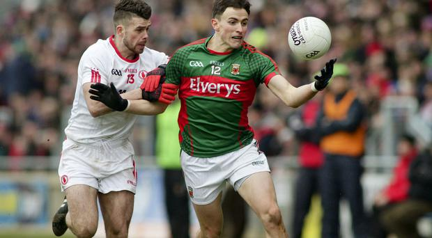 Holding on: Mayo's Jason Doherty and Tyrone's Darren McCurry clash at Castlebar yesterday