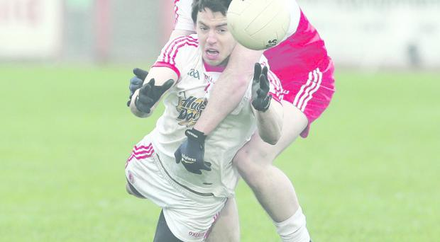 Derry's Dermot McBride gets up close and personal with Matthew Donnelly of Tyrone during the McKenna Cup semi-final