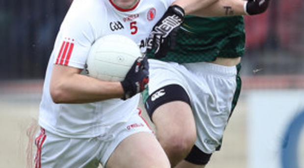 On the run: Tyrone's Ronan McNabb shrugs off Graham Reilly of Meath