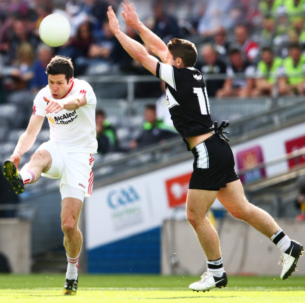 On target: Tyrone's Sean Cavanagh fires over a point under pressure from Sligo's Brian Curran at Croke Park