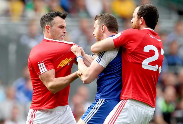 Gripping affair: Monaghan's Owen Duffy clashes with Cathal McCarron and Justin McMahon of Tyrone