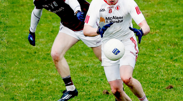 Handing the initiative: Colm Cavanagh of Tyrone clashes with Declan Kyne