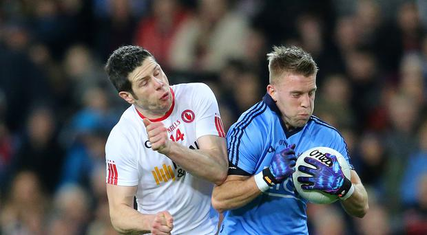 Up close: Tyrone's Sean Cavanagh (left) and Dublin's Jonny Cooper battle it out