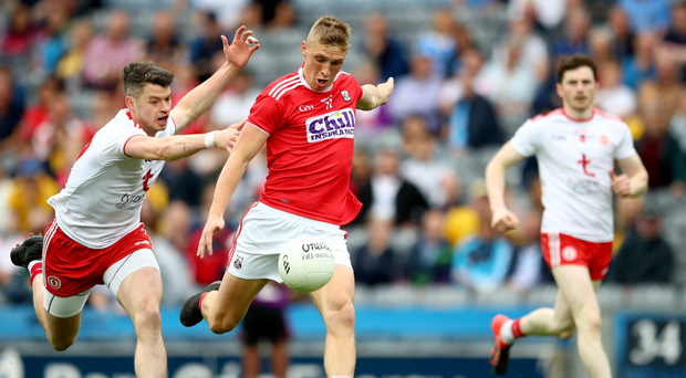 Under pressure: Tyrone ace Richard Donnelly attempts to put off Cork's Sean White
