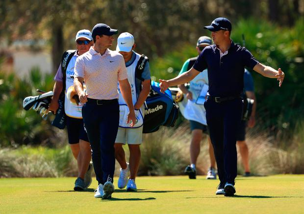 Rory McIlroy chats to playing partner Justin Thomas during his first round at The Concession GC.