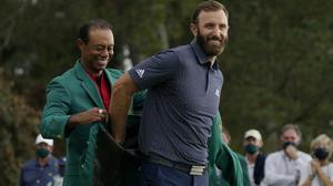 Tiger Woods helps Masters' champion Dustin Johnson with his green jacket (AP Photo/Charlie Riedel)