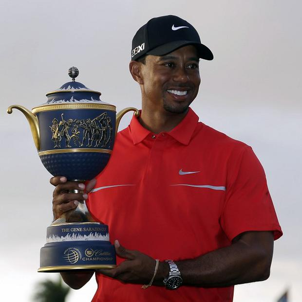 Tiger Woods poses with his trophy after winning by two shots (AP)