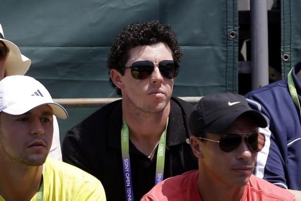 Golfer Rory McIlroy, pictured here on Saturday 23 March 2013 watching his girlfriend Caroline Wozniacki play in the Sony Open tennis tournament in Florida, is no longer ranked no 1 golfer