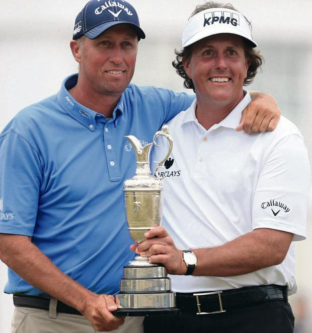 Phil Mickelson holds the Claret Jug along with his caddie Jim Mackay after his win at Muirfield