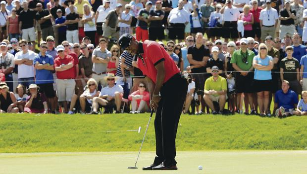 A true champion: Tiger Woods hits a putt, watched by an huge crowd, during his final round