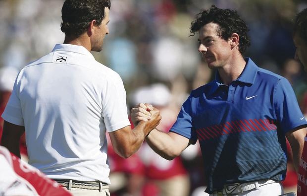 Tight finish: Rory McIlroy is congratulated by Adam Scott, the man he pipped to the Australian Open crown on Sunday