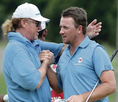 Winning start: Graeme McDowell is congratulated by European captain Miguel Angel Jimenez after his fourball match in Malaysia