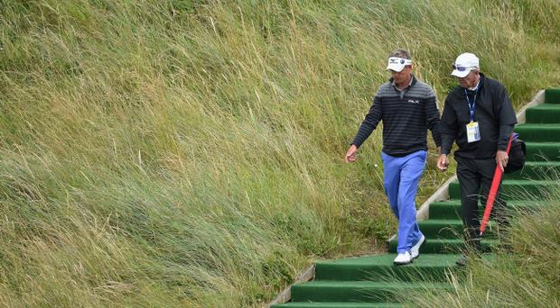 Luke Donald of England and his Coach Chuck Cook walk together during a practice round prior to the start of The 143rd Open Championship at Royal Liverpool
