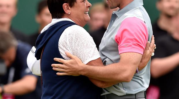 Rory McIlroy's mother Rosie rushes onto the 18th green to hug her son after he won The Open at Hoylake yesterday