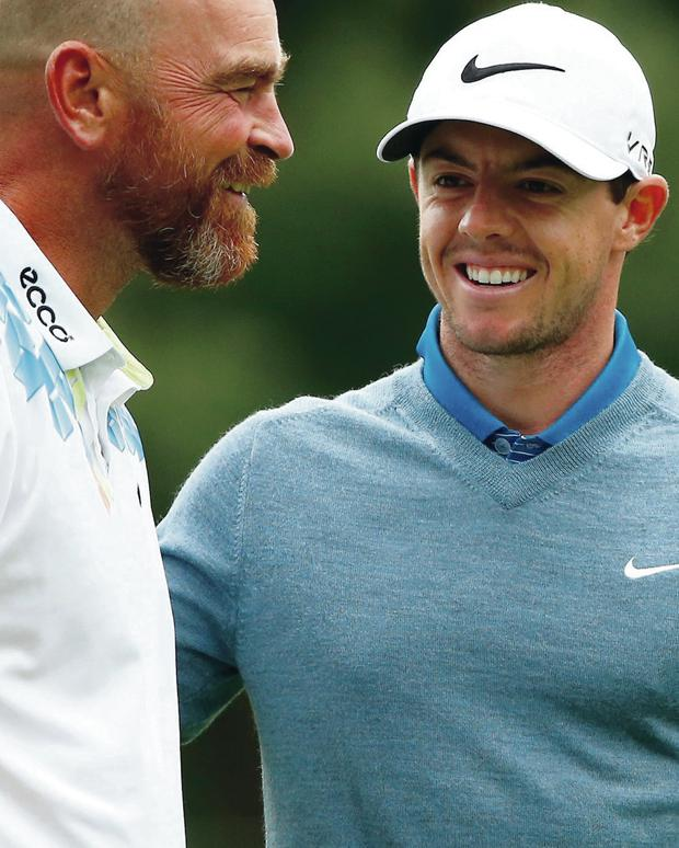Smiles better: Rory McIlroy has a laugh with Thomas Bjorn on the practice course yesterday