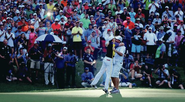 Moment of glory: Rory McIlroy embraces caddie JP Fitzgerald after sinking the putt to clinch his fourth Major at Valhalla
