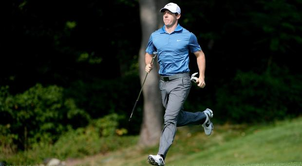 Man in a hurry: Rory McIlroy races down to one of the greens during yesterday's pro am event
