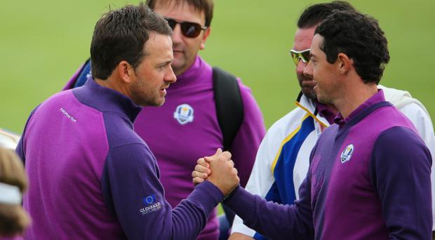 Team spirit: Rory McIlroy shakes hands with compatriot and Europe colleague Graeme McDowell yesterday