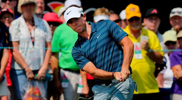 Powers of recovery: Rory McIlroy hits his third shot on the ninth hole yesterday