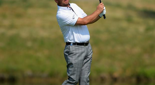 High hopes: Graeme McDowell plays his second shot on the first fairway yesterday