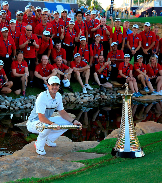 Number one: Rory McIlroy poses with the DP World Tour Championship trophy and a group of course marshals