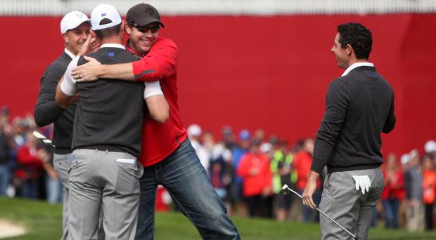Spectator David Johnson hugs Justin Rose after winning a bet by holing a putt in practice at the Ryder Cup