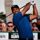 Testing time: Tiger Woods tees off during his five over opening round in Dubai