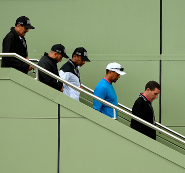 Exit: An injured Tiger Woods departs the Omega Dubai Desert Classic