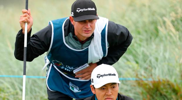 Eyeing it up: Daniel Im gets a close look at one of the greens